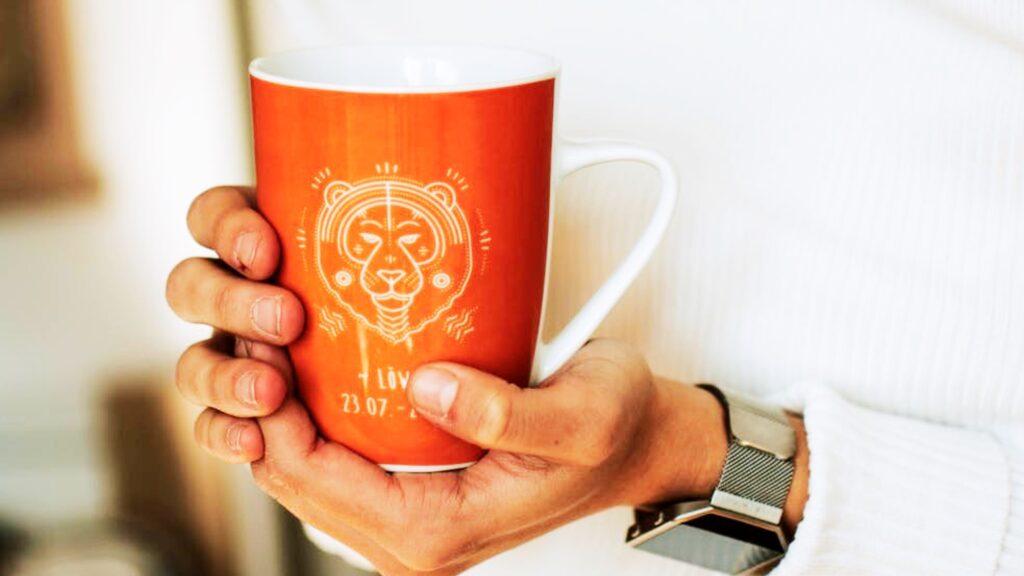 Kvinnohänder som håller en kopp