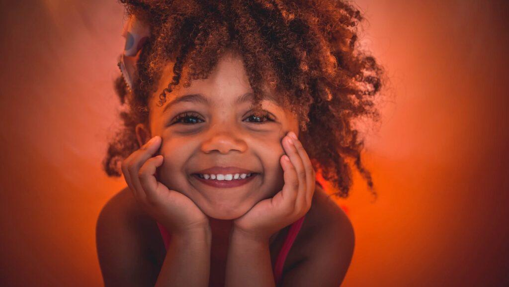Flicka med ansiktet i händernaoch ett stort leende